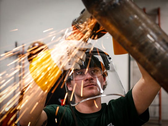 Brad Leo, an apprentice helper, grinds a pipe at the