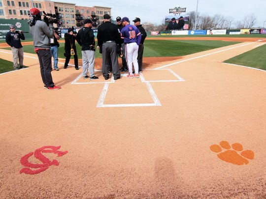 Clemson head coach Monte Lee talks with umpires before the South Carolina at Fluor Field in Greenville.