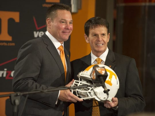 Tennessee athletics director Dave Hart, right, gives a helmet to new football head coach Butch Jones, left, during a press conference introducing Jones in the Peyton Manning Locker Room Complex at Neyland Stadium Friday, Dec. 7, 2012. (News Sentinel file photo)