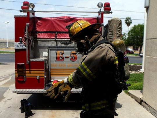 A Corpus Christi firefighter inspects his equipment.