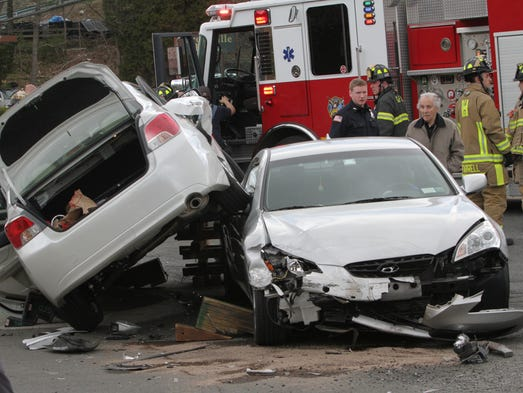 The driver of the vehicle on the right is followed by a police officer as he walks away from the two car accident that occurred near the intersection of South Healy Avenue and Central Park Avenue in Scarsdale April 23, 2014. Rodrigo Batista, of Mount Vernon who is not in the photo,  arrived shortly after the accident occurred and said the driver of the second vehicle was an elderly woman and she didn't appear to be seriously hurt either.