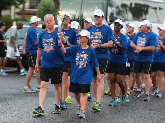 Special olympian Maria Brandt, from Pennsyvania and Icelandic law enforcement officer Gummi Sigurdsson, carry the torch during the Law Enforcement Torch Run's Final Leg for 2015 Special Olympics World Games on Saturday in Palm Springs.