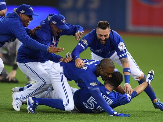 Toronto Blue Jays' players mob Russell Martin (bottom) after he drove in the winning run against the Texas Rangers during tenth inning game three American League Division Series action, in Toronto on Sunday,  Oct. 9, 2016. (Frank Gunn/The Canadian Press via AP)