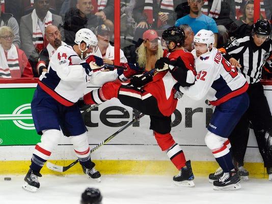 Ottawa Senators center Kyle Turris (7) is tied up between Washington Capitals defenseman Brooks Orpik (44) and Evgeny Kuznetsov (92) during the first period of an NHL hockey game in Ottawa, Ontario, Thursday, Oct. 5, 2017. (Adrian Wyld/The Canadian Press via AP)