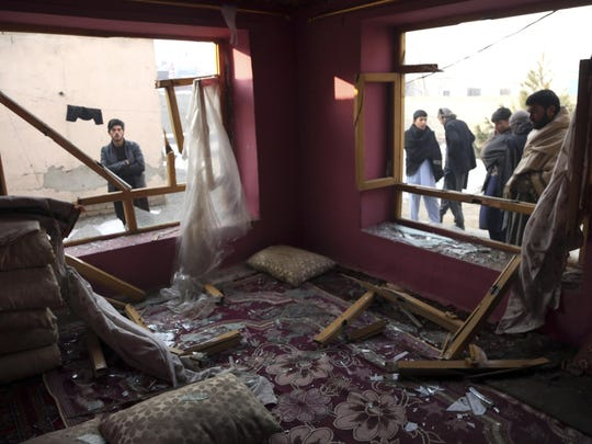 Afghan villagers stand near a destroyed house after an attack in Kabul, Afghanistan, Jan. 15, 2019. A Taliban suicide bomber detonated an explosive-laden vehicle in the capital Kabul on Monday evening, according to officials.