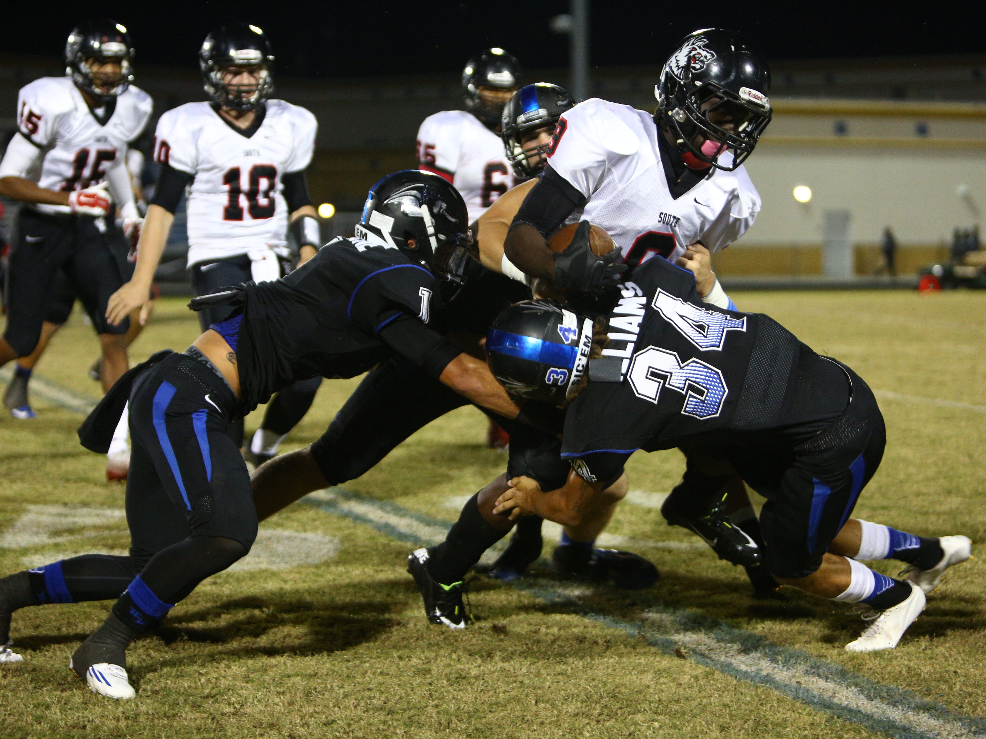 South Fort Myers' E'quan Dorris is tackled by Baker's Brennan Williams (34), Austin Maimone (1) and Zach Yankovich (42) during their game Friday night.