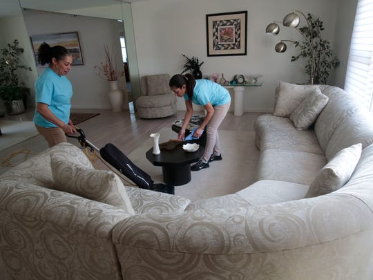 Margrita Cabrera and Yasmin Suriel, who works for Merry Maids, clean a home in New City on Wednesday.