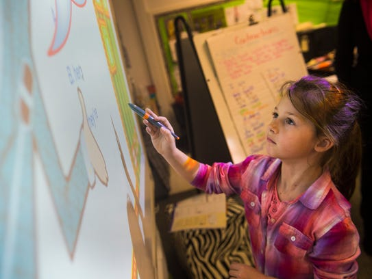 Student Sarah Loveless, 7, selects an answer on the