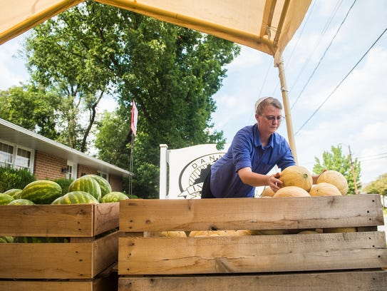 Employee Angela Birt arranges produce at the Five Points