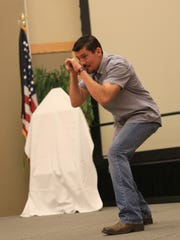"Kris ""Tanto"" Paronto mimic a shooting position Monday at Dixie State University as he speaks about the Sept. 11, 2012, attacks on U.S. compounds in Benghazi, Libya."