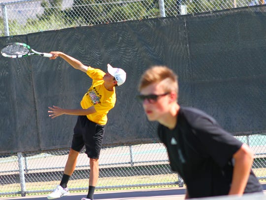 Alamogordo's Keanu Tran, left, serves a ball during doubles play as partner Leander Reig watches on.