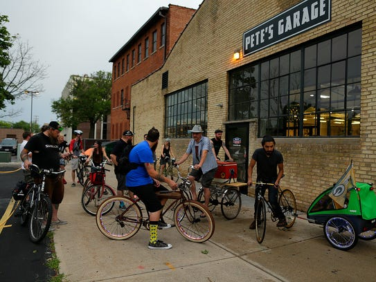 A group of bicyclists gather outside Pete's Garage
