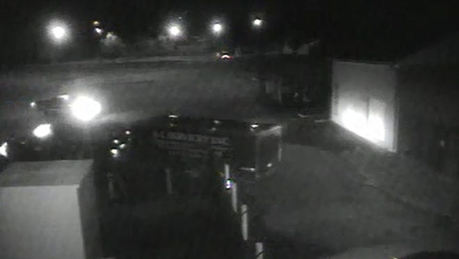 Video surveillance shows two trucks and trailers exiting a storage area on Tabor Road as a security guard watches.
