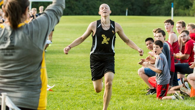 Tommy Laudani is cheered on as he nears the finish line during a cross country meet at Bermudan Springs on Thursday, September 7, 2017. Laudani, a senior at Delone Catholic, was running in his first race after being diagnosed with a rare form of cancer last November. In the last 10 months, he has undergone two major surgeries, chemo therapy and radiation treatment.