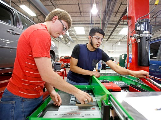 Jordan Martin, left, 19, and Osvaldo Acosta, 18, both of Farmington, grab tools and work on a wheel alignment on Tuesday during class in the automotive garage at the San Juan College School of Trades and Technology building in Farmington.