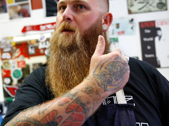 Jesse Rogers, a former oilfield worker who became a barber last year, explains how he applies beard oil on Wednesday at Main Barber Shop II in Farmington.