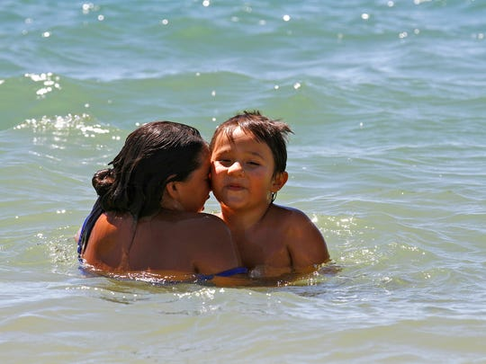 Elliana Chavez and her brother, Jakie Chavez, play in the water at Farmington Lake on Monday.