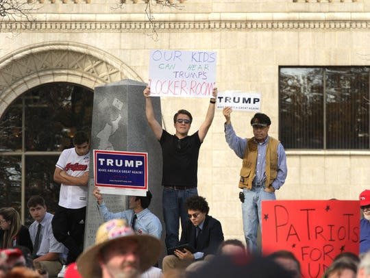 A protestor holds up a sign in the back of a rally