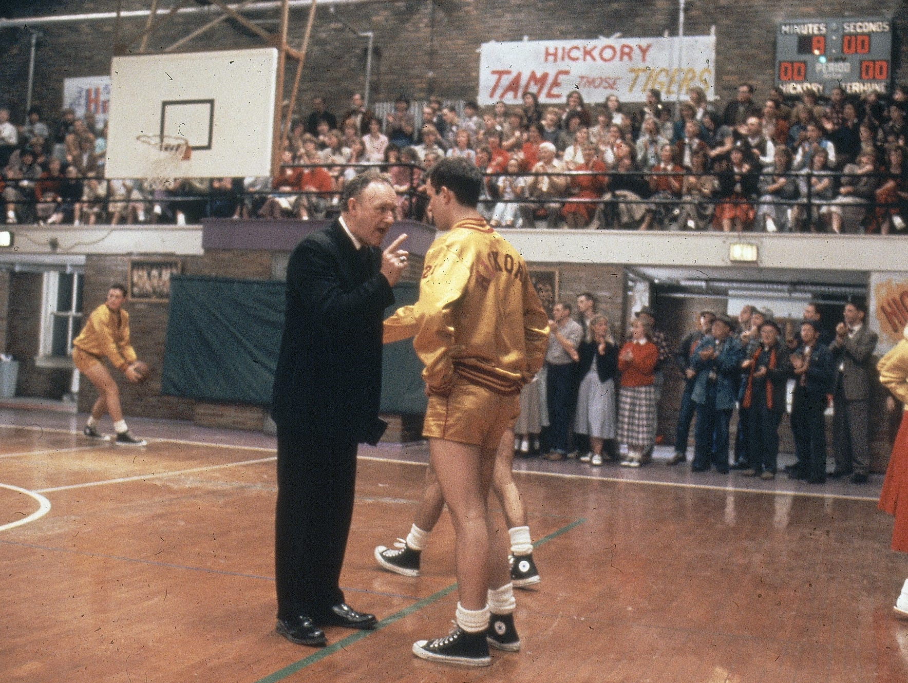 "Actor Gene Hackman (left), as coach Norman Dale, talks to a player on the court in the 1986 movie ""Hoosiers."""