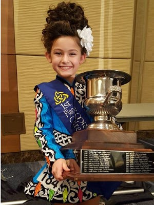 Ellie Maddox, 7, of Sioux Falls poses with a traveling trophy after winning her age division at the Mid-America Regional Championships for Irish dancing.
