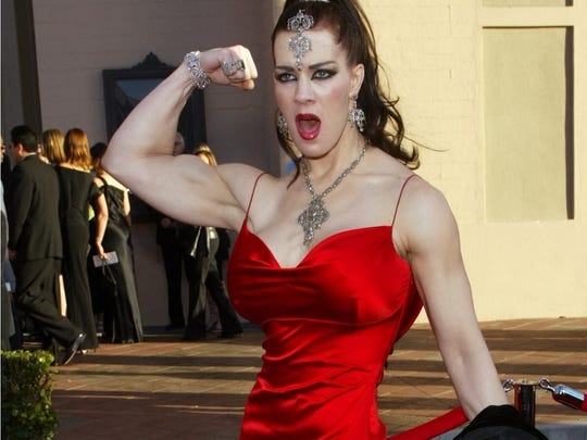 In this Nov. 16, 2003 file photo, Joanie Laurer, former pro wrestler known as Chyna, flexes her bicep as she arrives at the 31st annual American Music Awards, in Los Angeles. Chyna, the WWE star who became one of the best known and most popular female professional wrestlers in history in the late 1990s, has died.