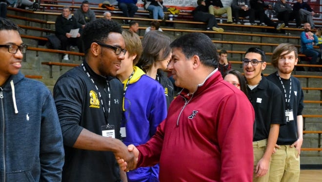 Rob Manuel (right), president of the University of Indianapolis, congratulates Jerome Hilliard from Christel House Academy South. Hilliard is among students who are in line to receive scholarships from UIndy.