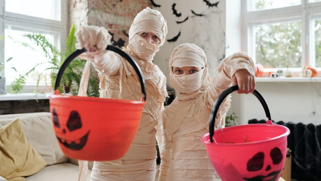 Children in costumes holding out plastic buckets for trick-or-treating.
