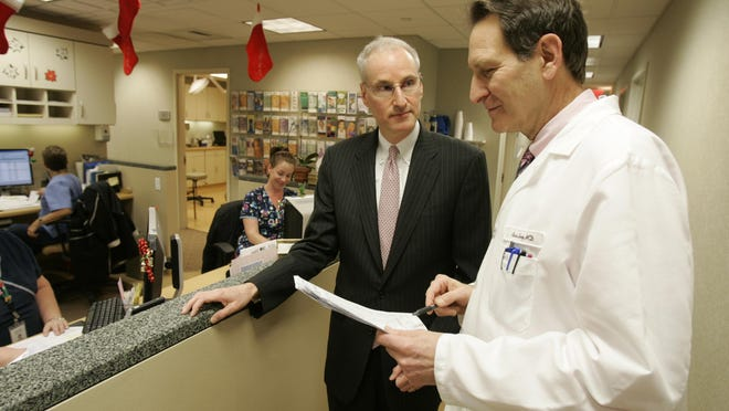 Scott D. Hayworth, M.D., the president and chief executive officer of the Mount Kisco Medical Group, center, chats with Ross Levy, M.D. in the dermatology department Dec. 8, 2010.