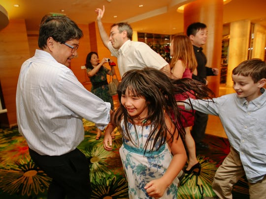 Dr. Don Liu, left, dances with his youngest daughter, Amelie, at the bat mitzvah of her older sister, Genevieve, in Shanghai. Dr. Don Liu drowned in Lake Michigan in August 2012 after he dove in to help two young boys who were struggling. The boys made it safely back to shore, but Liu was pulled under by a rip current.