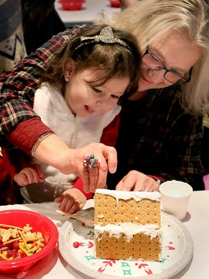 In this file photo, Carlene Ahrens, 2, enjoys watching her grandmother, Tammy Wiens, place items on the roof of her gingerbread house during the Gingerbread House Decorating event sponsored by Hutchinson Rec.