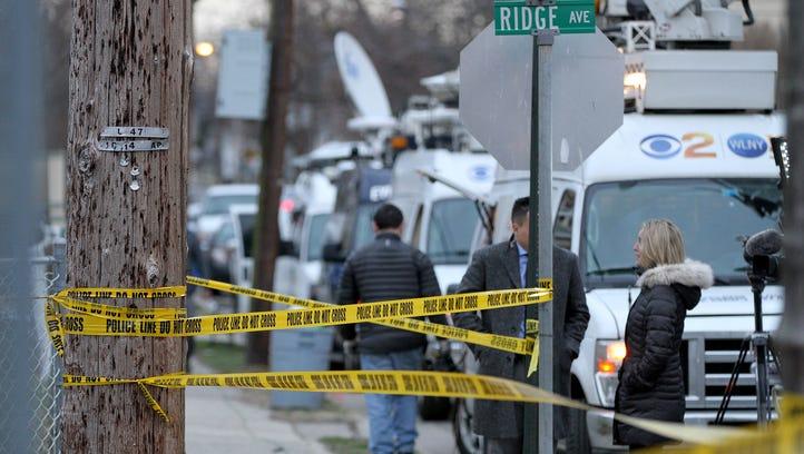 Media trucks line up near the scene of the fatal shooting