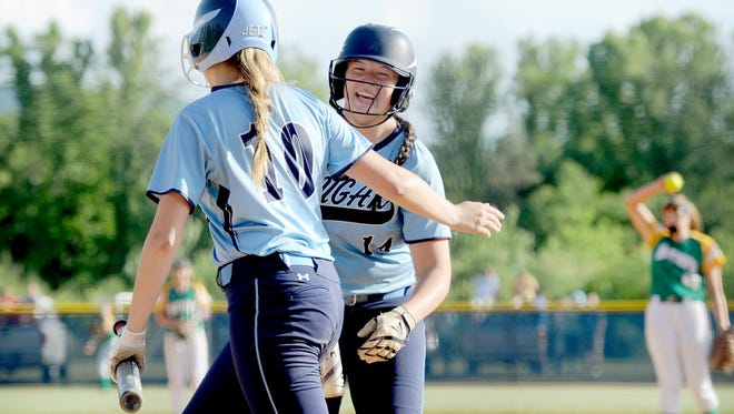 Jordan Harris and Katie Grace Olinger (10) celebrate during Tuesday's 12-2 playoff win over West Iredell in Candler.