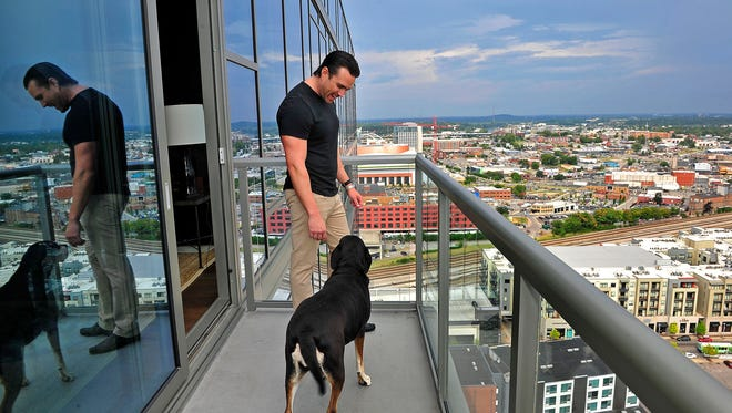 Twelve Twelve condo resident Parker Turner poses for a photograph with his dog Bella on the balcony at his condo.