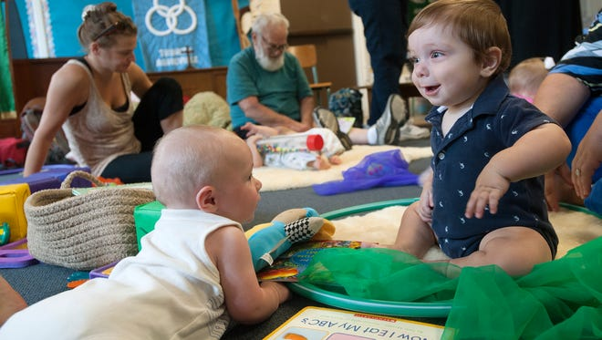 Camden Griffis, 4 months, left, and William Christie, 8 months, play together during a Buncombe Partnership for Children Play and Learn infant and toddler group meeting at Trinity Episcopal Church in 2015. The organization is now partnering with other groups to increase access to preschool.