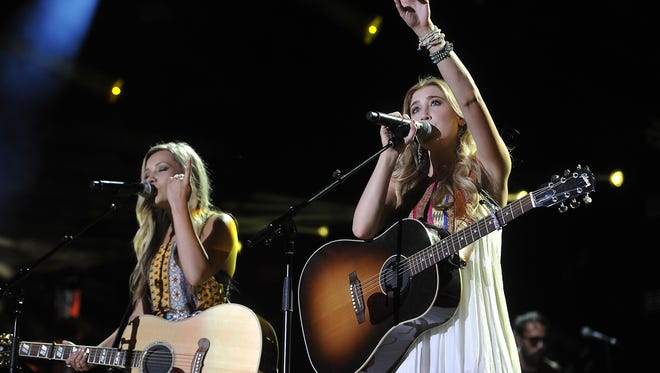 Taylor Dye, left, and Madison Marlow of Maddie & Tae perform during the 2015 CMA Music Festival.