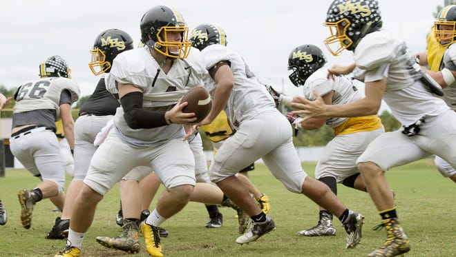 Dalton Kent hands off to a teammate Monday during football practice in Murphy.