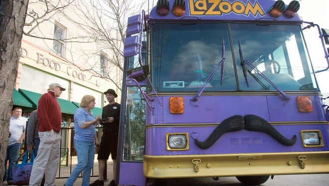Wyman Tannehill guides tourists onto the big purple bus for a LaZoom Tour departing from the French Broad Food Co-op.