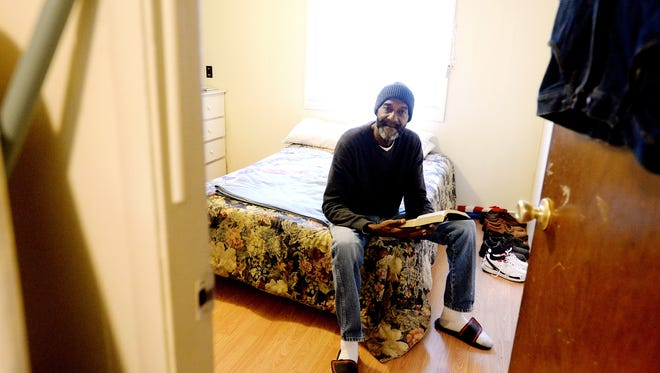 Bobby Lewis sits on the edge of his bed with his bible in the trailer home he has lived in for about the past year in Woodfin on Tuesday. Lewis, a Vietnam War veteran, spent more than a decade homeless. Now that he has a home he says he devotes much of his time to studying the bible.