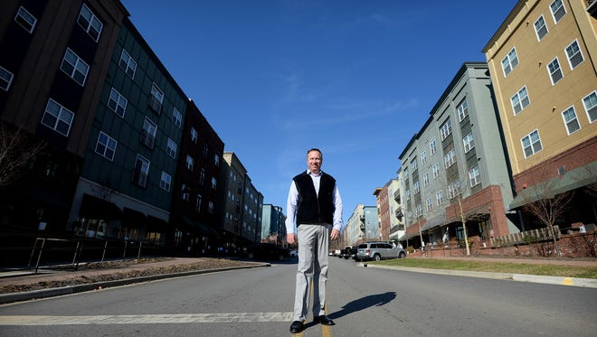 Kirk Boone, developer of Reynolds Village, stands in the middle of N. Merrimon Avenue in Reynolds Village in Woodfin on Thursday. The development is mixed-use with retail store on the main floor and lofts above.