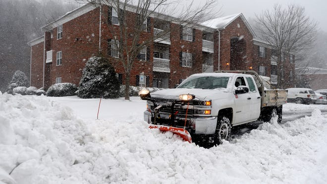 A truck with Landmark Landscapes plows the parking lot of Westmont Commons Apartments as heavy snow continues to fall on Friday, Jan. 22, 2016.
