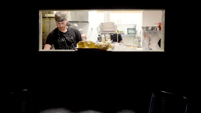 Matt McKenna is seen through a window into the kitchen of The Junction as he preps for dinner service on Friday, Feb. 19, 2016.