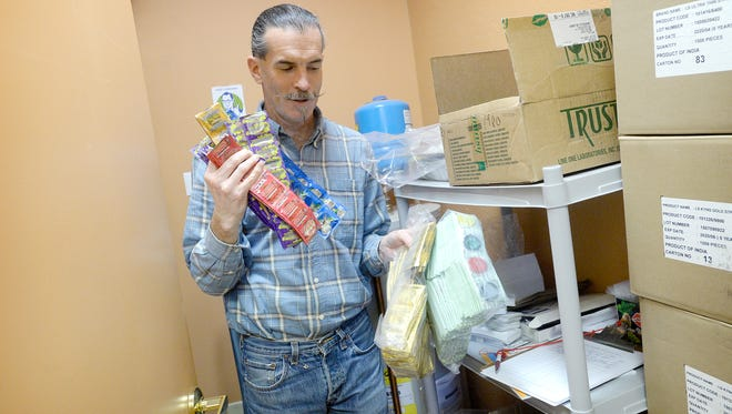 Michael Harney, a prevention educator with the North Carolina AIDS Project shows off some of the stock in the office's condom closet on Wednesday, Feb. 24, 2016. The condoms are distributed to various locations in the area and given out to anyone who wants them.