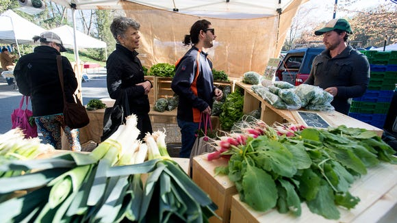 Patrons line up to purchase fresh produce at Second Spring's stand Saturday April 2, 2016 at the opening day of  Asheville City's outdoor market.