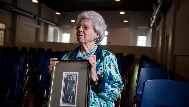 Sara Queen Brown, part of the Soco Gap Dancers, holds a photograph of her and her father Sam Queen, who founded the group, Tuesday May 10, 2016 in the renovated auditorium being named in her honor at the Folkmoot center in Waynesville.
