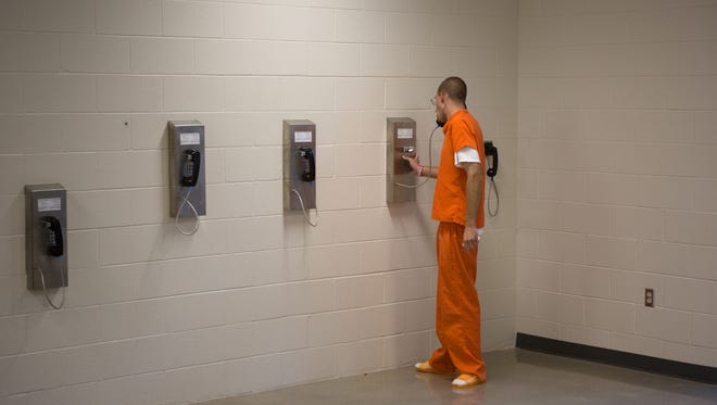 An inmate uses a telephone  at the Larimer County Jail on Oct. 9, 2014.