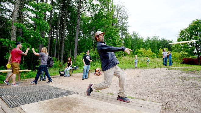 """Ryan Pickens, author of """"The Definitive Guide to Disc Golf,"""" throws a practice shot from the tee of the first hole before a tournament at Richmond Hill Park on Tuesday, May 17, 2016."""