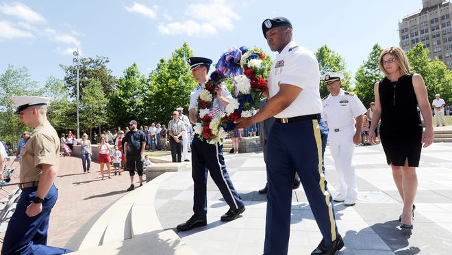 Sgt. James Crocker, left, and Staff Sgt. Rodney Garrett present a wreath during the 2015 Asheville-Buncombe Memorial Day ceremony.