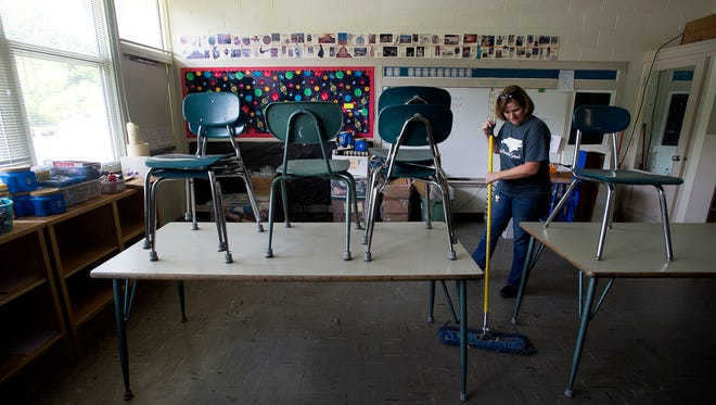 Lead custodian Sharon Chambers sweeps up an empty classroom June 13, 2016. Chambers has worked at Central for five years and will be headed to Canton Middle for the next school year.