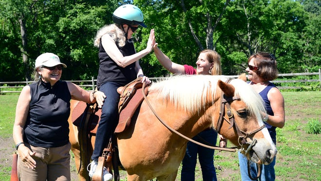 Jamie Henderson gives a high-five to Asheville Citizen-Times reporter Beth Walton from atop a horse as she does a horse therapy session with Equinox Horse Foundation celebrating national deaf-blind awareness month at Shaman Hill farm on Friday, June 10, 2016. Participants groomed the horses and then rode them with help from guiding volunteers.