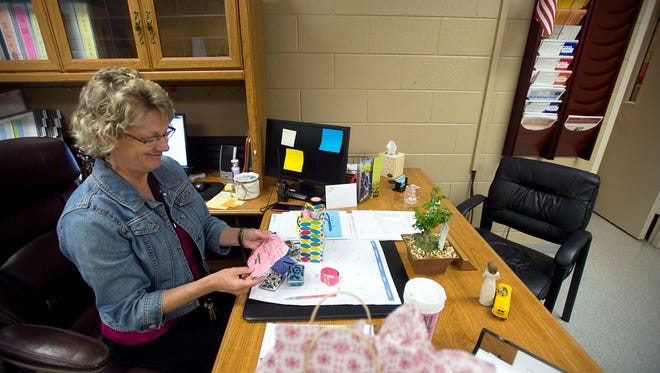 Principal Jeanann Yates reads a note from a student in her office June 13, 2016.